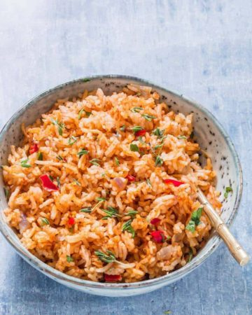 overhead view of jollof rice in a blue bowl with spoon in jollof rice