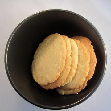baked cardamom biscuits in black bowl