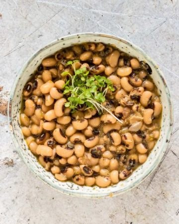 overhead view of black eyed beans in a bowl with greens on top