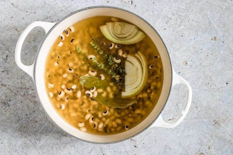 white pot containing cooked black eyed beans with sliced onion floating