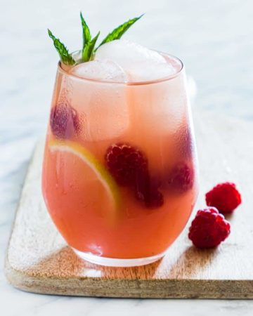 a glass of raspberry vodka lemonade garnished with mint and raspberries