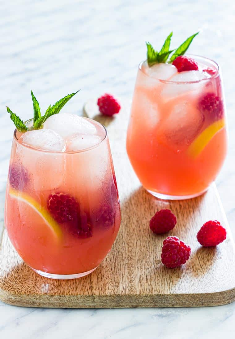 2 glasses of pink vodka lemonade on a table with mint and raspberries