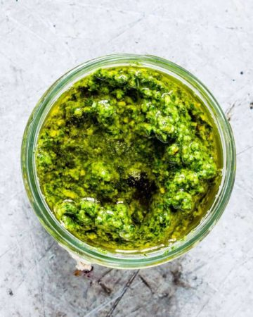 top down view of basil pesto in a glass jar
