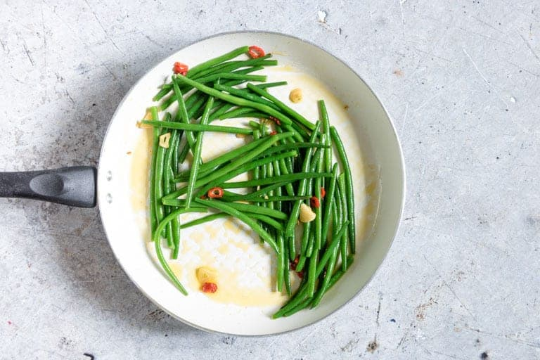 Chilli garlic green beans in a frying pan while making green bean recipe