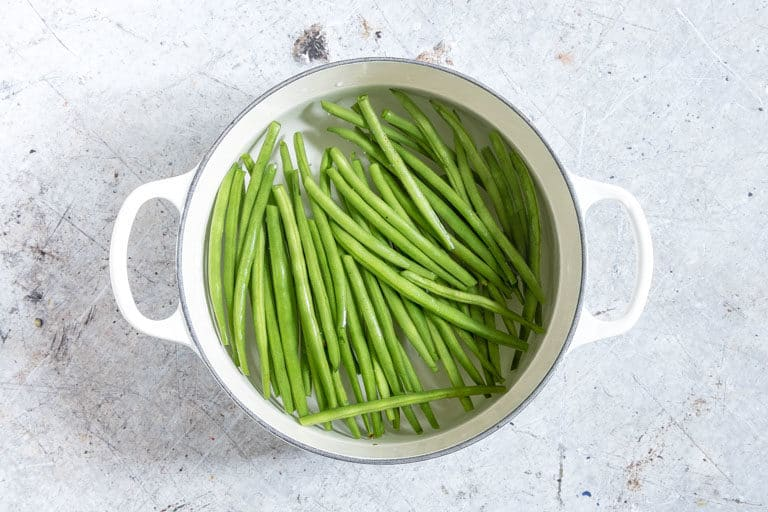green beans in a white pot with some water