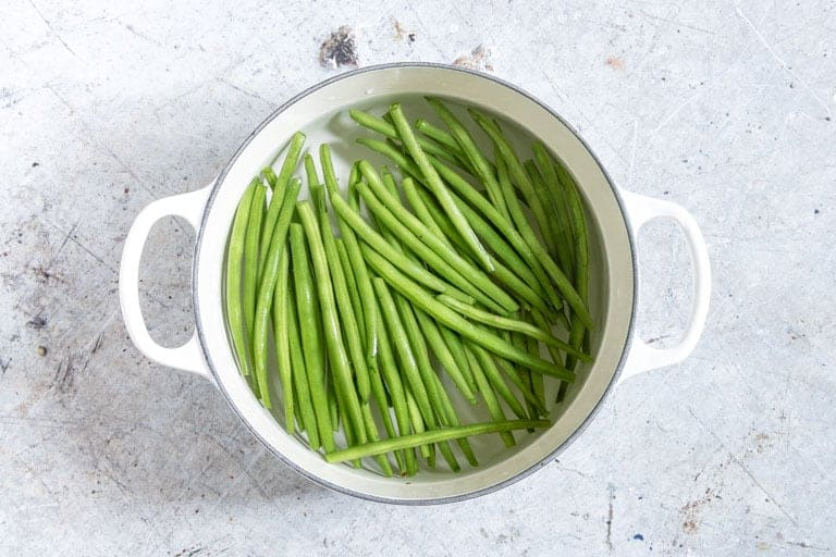 green beans in a white pot with some water for green bean recipe