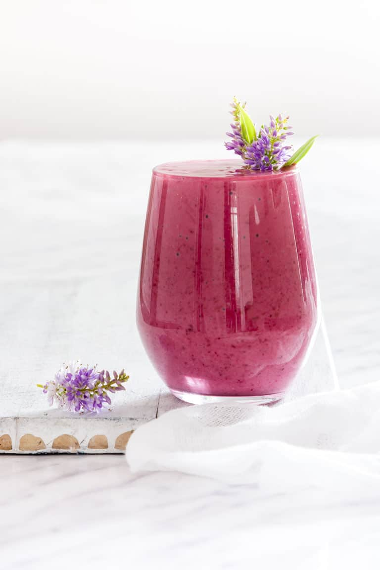 Blackberry Smoothie in a glass with a flower proper in it