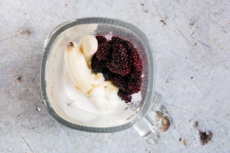 Ingredients for blackberry smoothie in a blender - banana, milk, yoghurt, blackberries