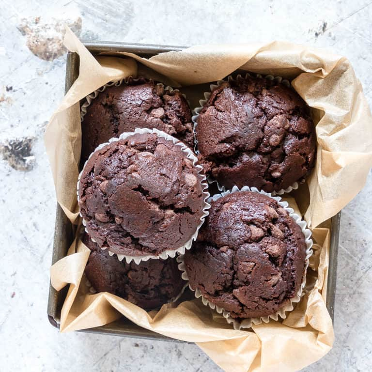 a container full of double chocolate banana muffins