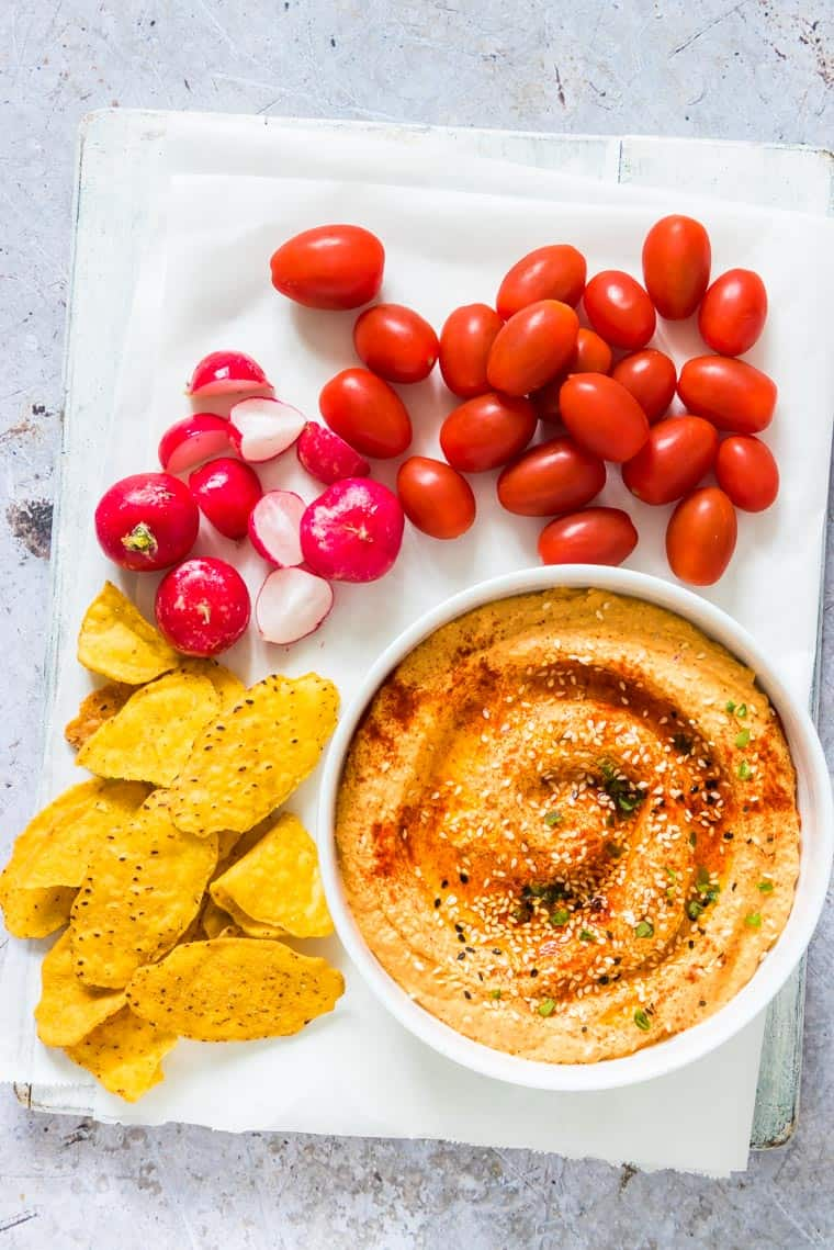 pumpkin hummus surrounded by radishes, tomatoes and tortilla chips