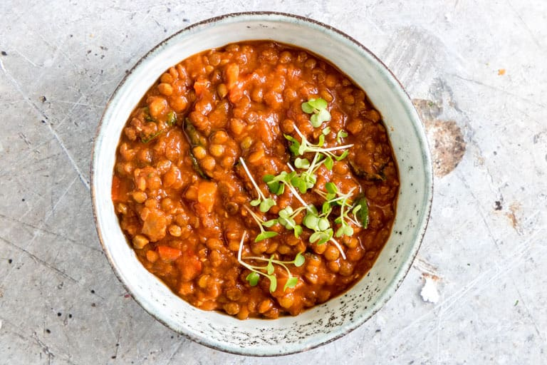landscape image of bowl of slow cooker lentil curry with crrss for garnish
