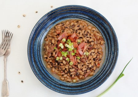 a bowl of hoppin john garmished with bacon and spring onions with 2 forks on the side