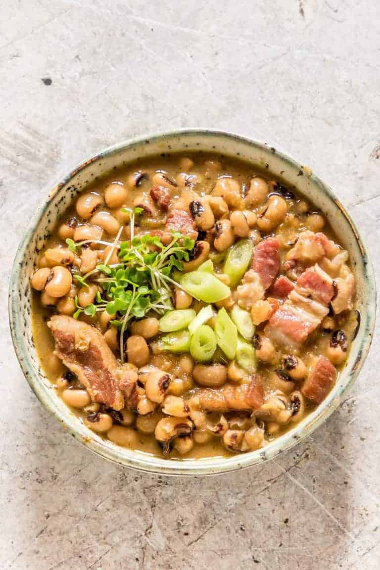 A bowl of Hoppin' John soup garnished with bacon, spring onion and cress