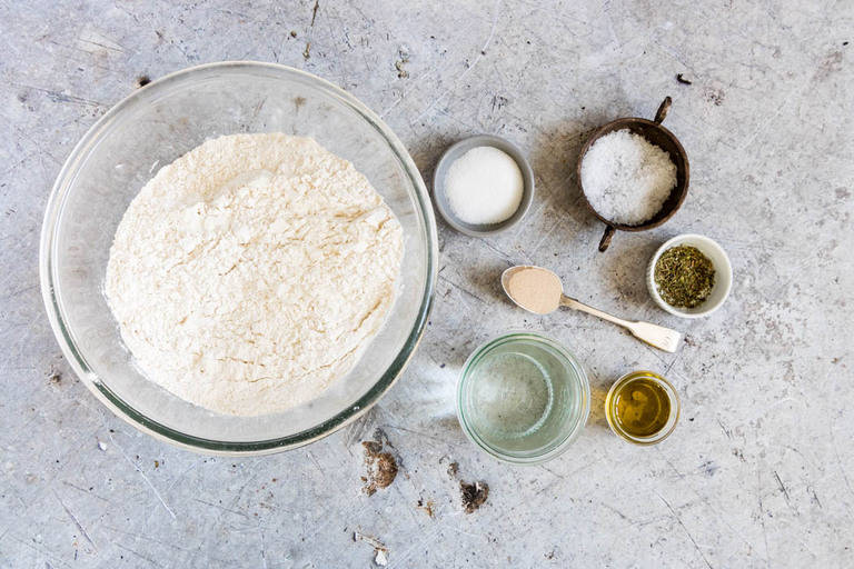Top down view of homemade italian pizza dough recipe ingredients - flour, salt, oil, water, yeast, sugar and herbs