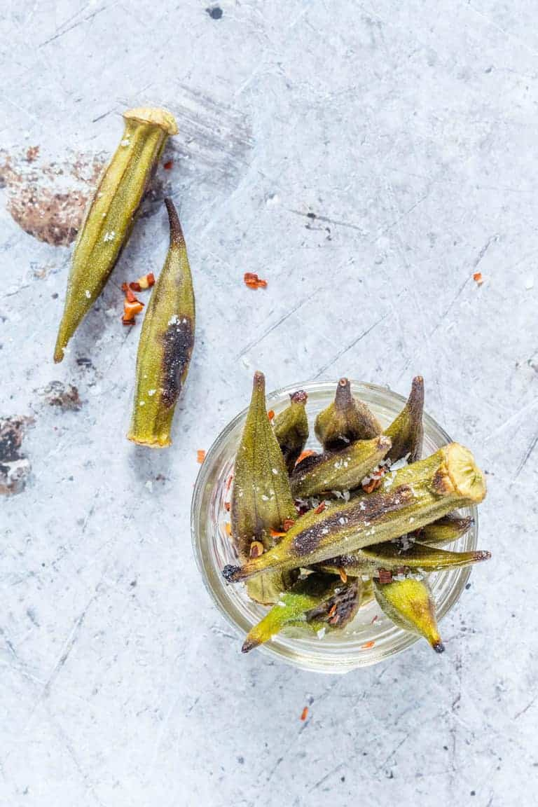 roasted okra in a glass jar next to two pieces of roasted okra on a counter