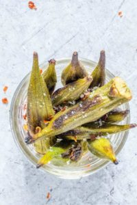 closeup overhead shot of roasted okra in a glass jar