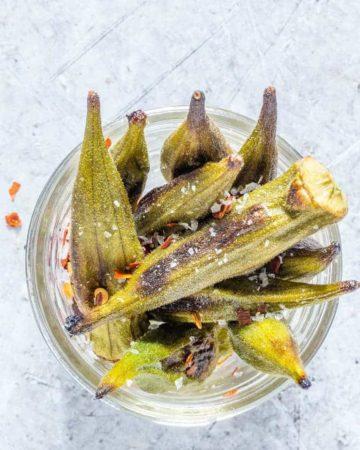 closeup overhead shot of roasted okra in a glass jar