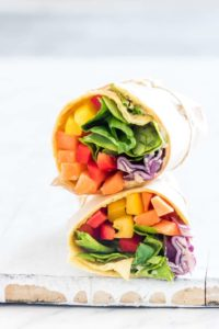 a rainbow vegetable tortilla wrap sliced in half