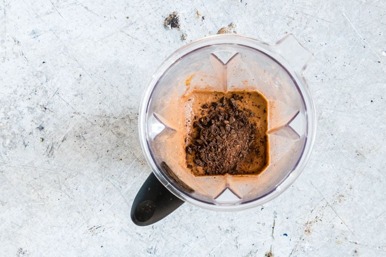 overhead view of chocolate hummus in a blender containing chocolate pieces