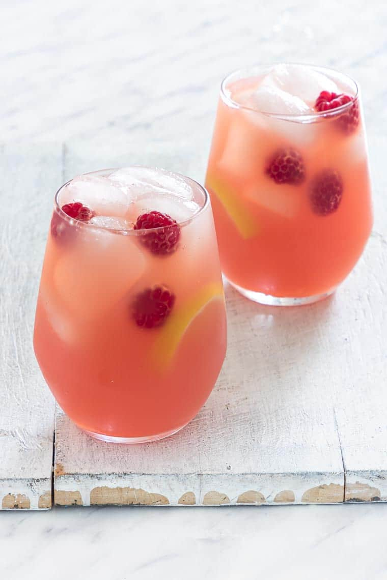 2 glasses of raspberry lemonade with garnishes