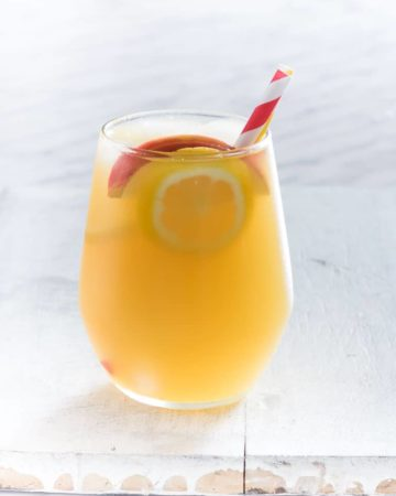 A glass of gin apple pie cocktail with apple and lemon slices