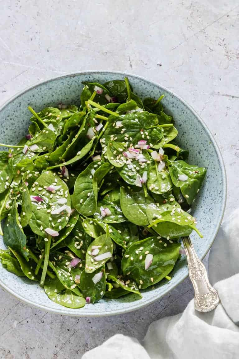 close up of easy sesame spinach salad recipe in a bowl with onion and sesame seeds