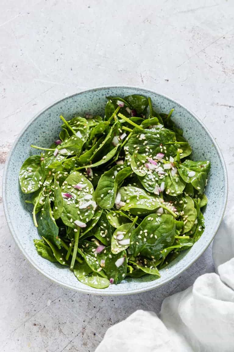 easy spinach salad recipe in a bowl with onion and sesame seeds