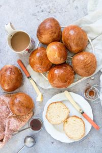 overhead view of orange cardamom buns on a rack, on a white plate, and on a towel