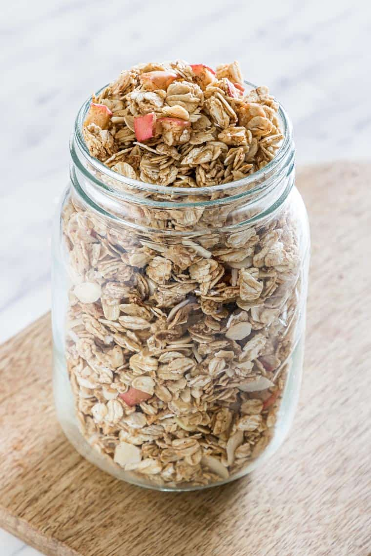 a glass jar full of cinnamon granola on a table