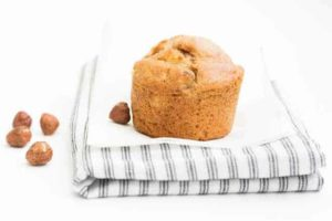 apple hazelnut muffins on a dish towel next to hazelnuts