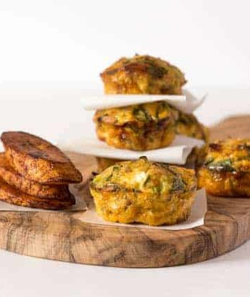 a pile of plantain frittata sitting on a cutting board separated by paper