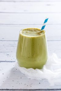 Matcha Smoothie (green Tea Smoothie) in a glass on a white table with a blue striped straw