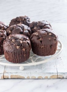 a set of orange chocolate chip muffins on a table