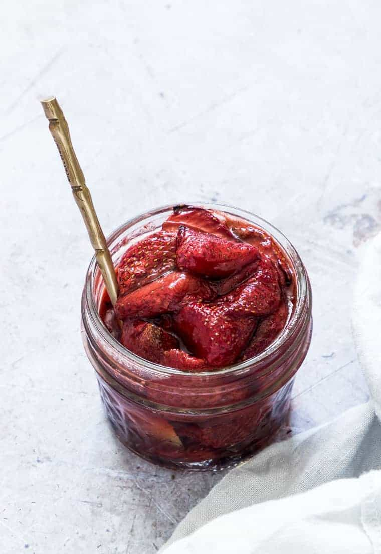 balsamic roasted strawberries in a glass jar with a gold spoon inside and ready to be served