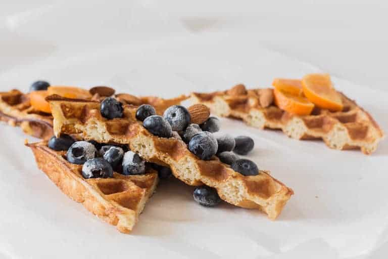 closeup of plantain waffles sliced with blueberries on top