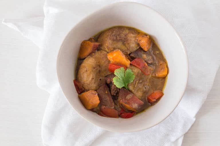 plantain curry with duck and sweet potatoes in a large white bowl