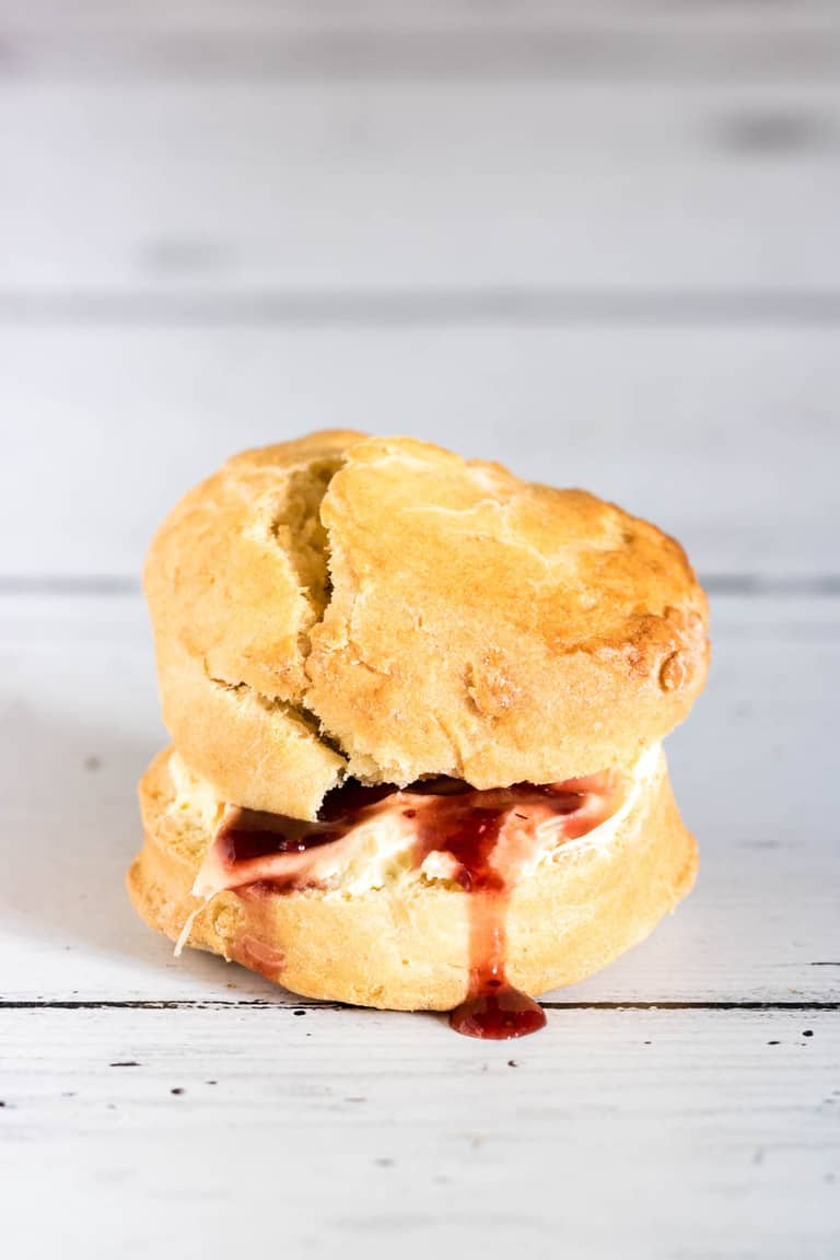 A lemon scone with cream and jam leaking out