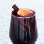 a single glass of instant pot mulled wine garnshed with clementines and a cinnamon stick