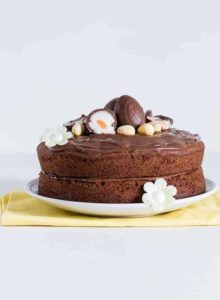 A side on view of a nutella cake with nutella frosting topped with cadbury creme eggs