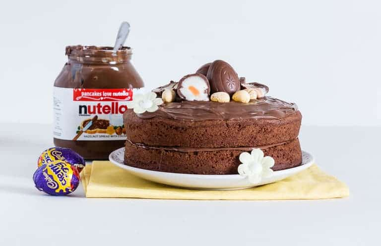 Easy Nutella Cake topped with nutella frosting and some cadbury creme eggs, with a jar of nutella at the back