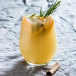 A glass of warm spiced pear juice garnished with fruit and rosemary