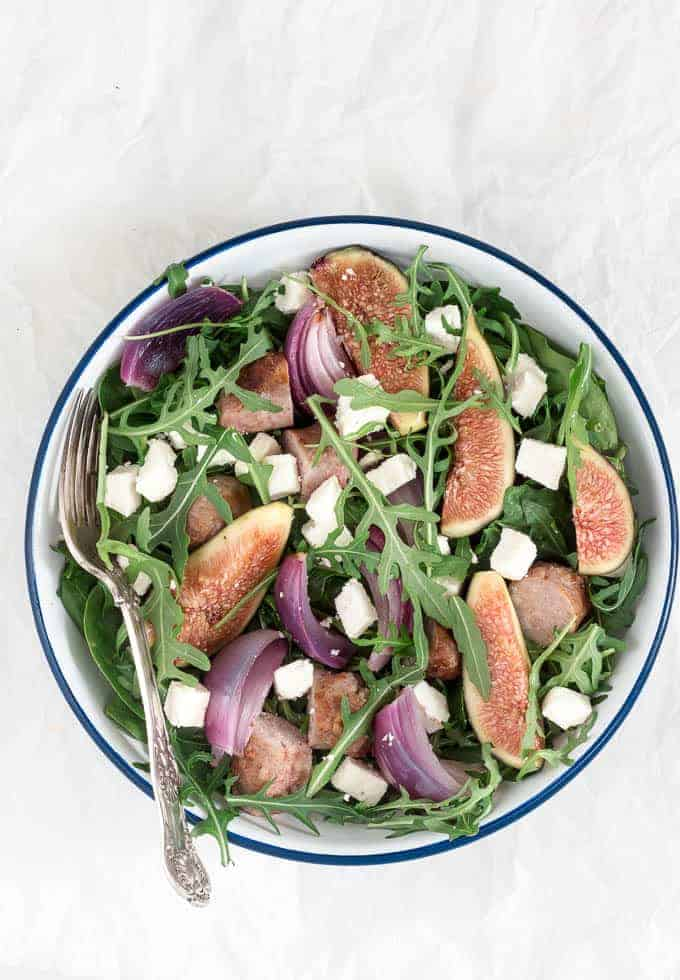 overhead view of white bowl containing sausage salad with figs, feta, red onions and a fork
