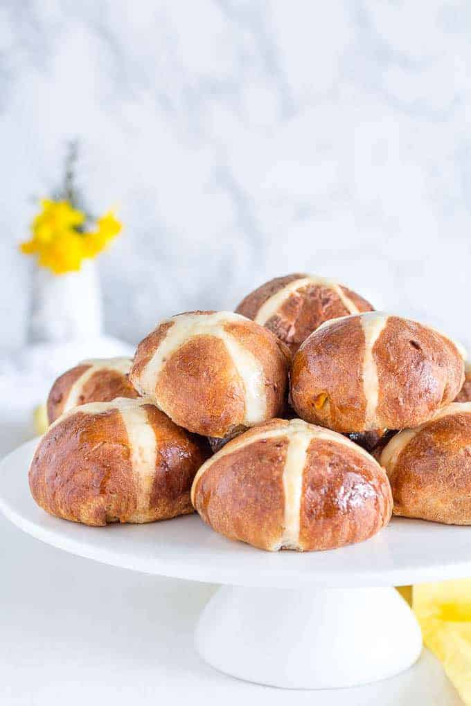 Hot Cross Buns Recipe - Hot cross buns on a cake tray with yellow flowers