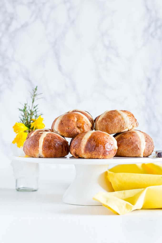 Hot Cross Buns Recipe - Hot cross buns on a cake tray with flowers and a yellow cloth.