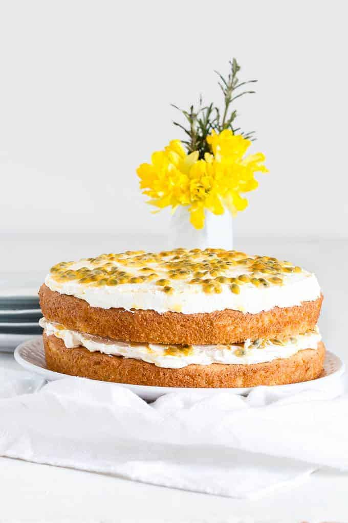 two layer lime and passion fruit cake on white towel in front of beautiful yellow flowers