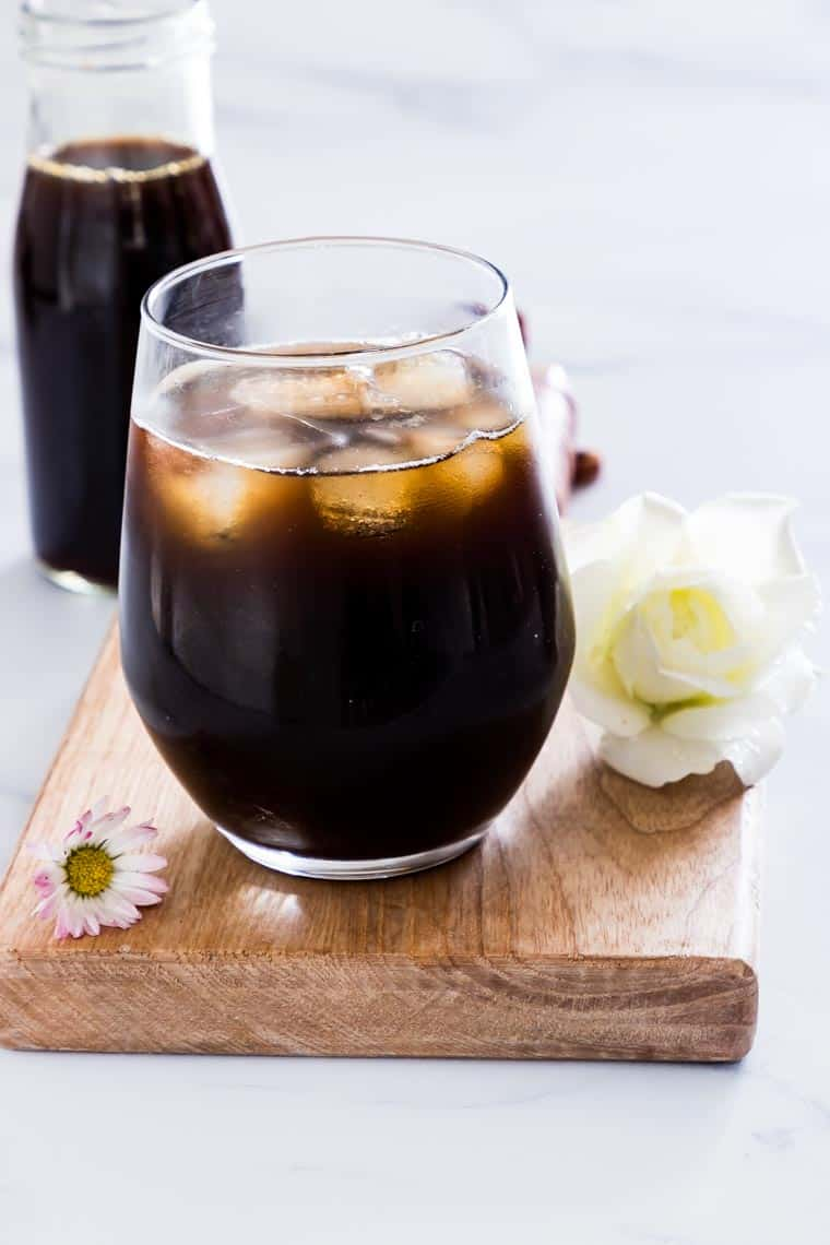 close up of instant pot iced coffee concentrate in a glass and a bottle with flowers