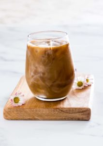 A Glass of Iced Coffee with flowers around it
