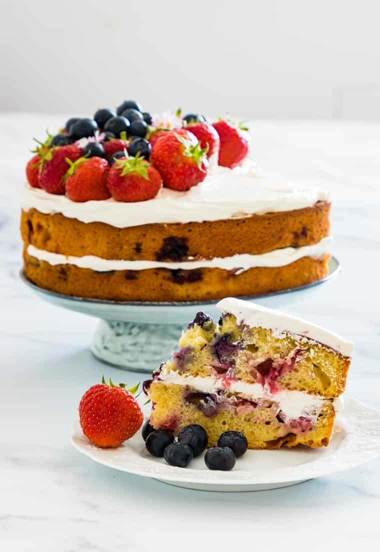 strawberry blueberry cake on a light green cake stand with one slice removed and served on a white dessert plate