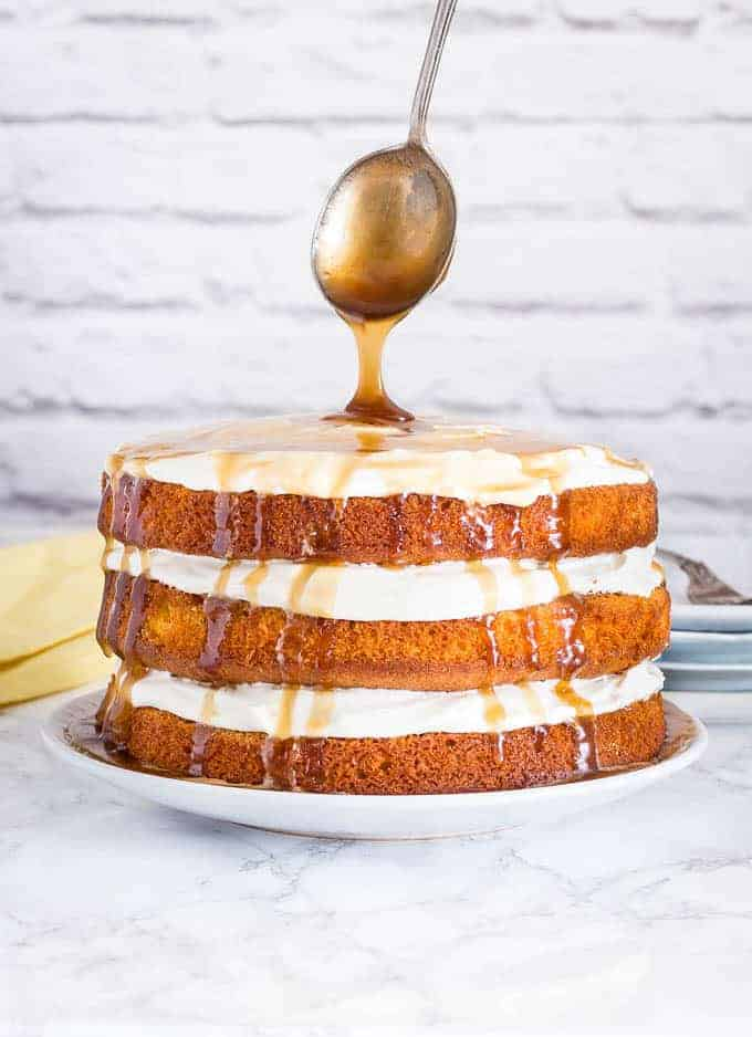 mango cake being drizzled with caramel sauce with a spoon