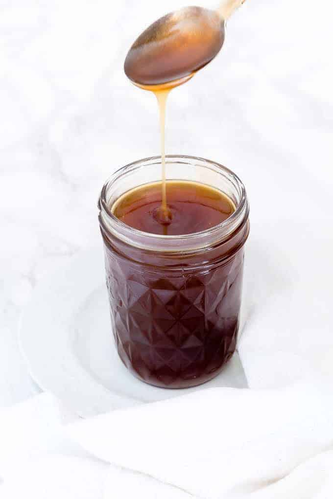 spoon drizzling coconut caramel sauce into a canning jar on a white plate